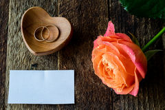 Wet rose, heart and wedding rings. On a wooden table Royalty Free Stock Photography