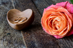 Wet rose, heart and wedding rings Stock Photo