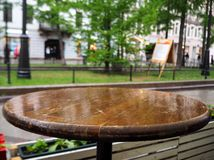 Wet round wooden table with drops of rain stock image