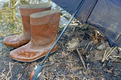 Wet rubber boots under the umbrella Royalty Free Stock Photos