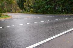Wet rural asphalt road with dividing line Stock Photos