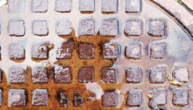 Wet rusty sewer hatch. Royalty Free Stock Photo