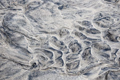 Wet sand abstract. Grey and beige abstract background of wet sand texture formed by flowing water on beach Royalty Free Stock Images