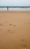 Wet sand beach with footprints and a remote man Stock Image