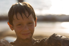 Wet sand dirty boy kid smiling while playing at beach.Warm sunset light. Family summer travel vacations at sea or ocean Royalty Free Stock Images