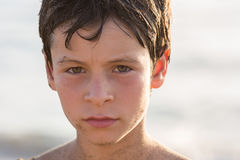 Wet sand dirty serious boy kid at beach.Warm sunset light. Family summer travel vacations at sea or ocean Royalty Free Stock Photos