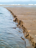 Wet Sand Eroding at the Beach Stock Images