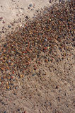 Wet sand and pebbles on Baltic beach. Natural background. Stock Photos