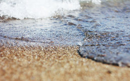 Wet sand and waves on the sea Stock Photography
