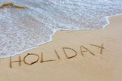 The word holiday in the sand of the beach written with waves of surf stock photography
