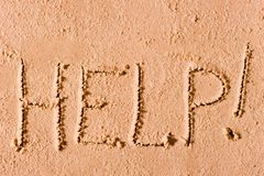On the wet sand written the word. Help! by the sea Royalty Free Stock Image