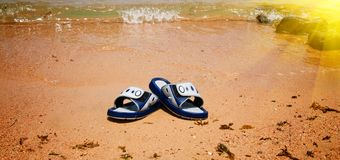 Wet sandals next to the sea. Stock Image