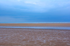 Wet sandy beach,  blue sky and the sea, Northern Sea, Holkham beach, United Kingdom. The Norfolk Coast Area of Outstanding Natural Beauty is a protected Royalty Free Stock Image