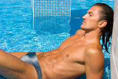 Wet sexy man. Young wet sexy muscular man lying relaxing in swimming pool Stock Photography