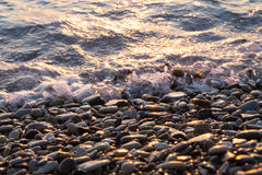 Wet shiny stones and small wave on the beach. Wet shiny stones and small wave on sundown on the beach. Close-up view stock image