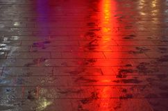 Wet sidewalk lit by red light beam stock images