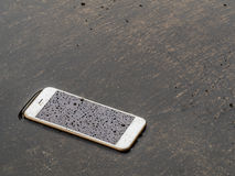 Wet smart phone dropped on flooding floor royalty free stock photos