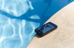 Wet Smart Phone On Pool Deck. A smart phone that has been splashed and damaged by water from the pool. Phone is sitting on the pool deck royalty free stock images