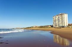 Wet Smooth Shoreline Beach Sand and Blue Coastal Skyline. Wet smooth shoreline beach sand with buildings  ocean and waves against blue coastal skyline in Kwa Stock Photos