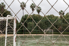 Wet soccer field seen through network. Stock Photos