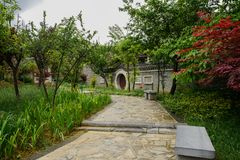 Wet stone path before old-fashioned enclosure in plants after ra. Wet stone path before enclosed old-fashioned buildings in plants and trees of cloudy spring stock photo