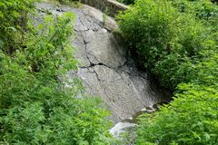 Wet stones of a waterfall in green grass and vegetation. Wet stones in the cracks of the waterfall in green grass and vegetation royalty free stock images