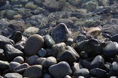 Wet stones on the seashore. Partly covered by the clear sparkling sea Stock Photos