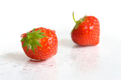 Wet strawberries. On a white surface Royalty Free Stock Photo