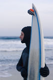 Wet surfer with surfboard standing on the sand Royalty Free Stock Image