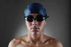 Wet Swimmer Portrait. Portrait of a male competitive swimmer over a light to dark gray background. Horizontal format. Athlete is wet like he just came out of the Stock Photo