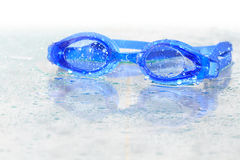 Wet Swimming Goggles. Blue wet swimming goggles on glass background with water drops royalty free stock photo