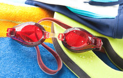 Wet swimming goggles and towel Stock Photo