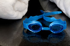 Wet swimming goggles and towels Royalty Free Stock Photo
