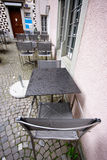 Wet tables and chairs in rainy day at pavement cafe Stock Photo