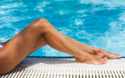 Wet tanned woman legs on a edge of swimming pool. Stock Photos