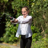 Wet Teenage Girl Squirts Water From Bottle. Wet teenage girl in white shirt and black legging squeezes water from plastic bottle Royalty Free Stock Image