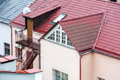 Wet tiled red roof with attic windows Stock Photos
