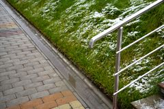 Wet tiled sidewalk at the beginning of winter. Lawn with green grass covered in snow. A gutter separates the lawn and the