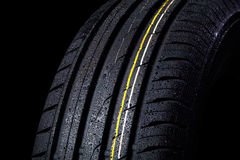 Wet tire. With asymmetric tread, close-up on a black background Royalty Free Stock Image