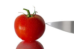Wet tomato with knife Stock Images