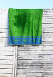 A wet towel, on a wooden fence, at the sea Royalty Free Stock Photo