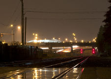 Wet Train Rails With Red Lights And Overpass Stock Photography