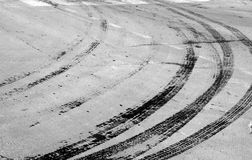 Wet tyre tracks on dirty asphalt road in black and white. Abstract background and pattern Stock Images