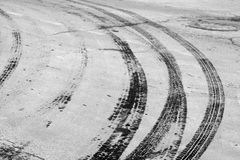 Wet tyre tracks on dirty asphalt road in black and white. Abstract background and pattern Royalty Free Stock Photos