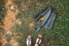 Wet umbrella with dry yellow leaf lying and female legs  red nails on the autumn ground, grass background. Fall season, concept. L Royalty Free Stock Photos