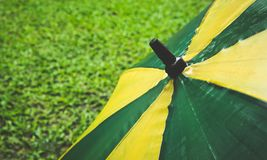 Wet umbrella and fresh green grass. Background Stock Photos