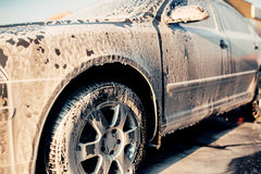 Wet vehicle in foam, automobile in suds, car wash. Carwash station Stock Image