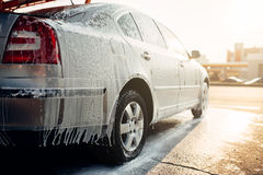 Wet vehicle in foam, automobile in suds, car wash. Carwash station Royalty Free Stock Images