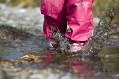 Wet weather. Child playing in water after raining Royalty Free Stock Photography