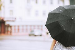 Wet weather. Autumn rain. Girl in a polka dots dress hold black umbrella. Raining in the city. Wet umbrella against the backdrop royalty free stock photography